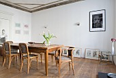 Antique, wooden chairs and dining table in dining room with gallery of pictures on floor