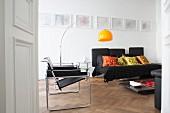 Weißes Wohnzimmer mit schwarzen Möbeln und einer gelben Bogenleuchte