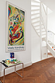 Classic side table below poster on wall of hallway with white, winding staircase to one side