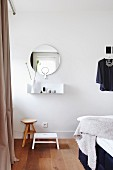 Minimalist wall-mounted shelf below round mirror above stools in bedroom