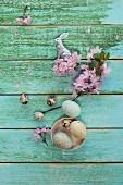 Ostereier in einer Schale, Wachteleier, silberner Osterhase und Kirschblütenzweig auf Holzuntergrund