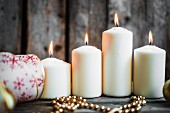 Vier brennende weisse Kerzen, unterschiedlich hoch