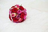 Bridal bouquet of roses on white blanket