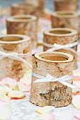 Tealight holders made from birch trunk segments ties with white ribbons