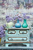 Dried, purple flowers in three colourful, glass vases on top of vintage chest of drawers against painted background