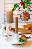 China candlestick with bird figurine, ice-skate ornament, stacked books and Christmas bauble hanging from sprig of holly