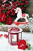 Kleine Windlaterne mit Rosenblüte im Kunstschnee, dahinter ein Deko-Schaukelpferdchen und Winterbeeren