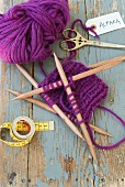 A piece of purple alpaca wool knitting with wooden needles