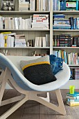 A sofa cushion with a knitted cover in a bucket chair in front of a bookshelf