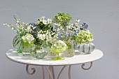 Arrangement of tiny vases of spring flowers on table