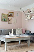 Coffee table painted pale grey and corner sofa below framed pictures on pink-painted wall