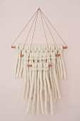 Wall-hanging made from knotted woollen yarn on copper rods