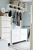 White narrow tallboy and chest of drawers under clothing hung from coat rack mounted on pastel blue wall