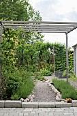 Simple wooden pergola over gravel garden path
