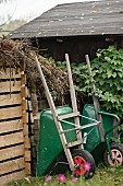 Two wheelbarrows outside garden shed