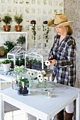 Woman wearing straw hat arranging white gerbera daisies in small glass vases