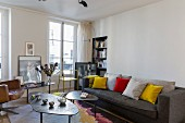 Set of coffee tables with amorphous tops and dark grey couch with colourful scatter cushions in living room