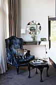 Black postmodern armchair and side table in corner of bedroom