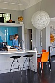 Woman at counter with integrated sink, bar stools and spherical designer lamp above dining area in designer kitchen