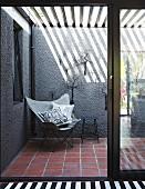 Blick durch Terrassentür auf Butterfly Sessel vor grauer Wand, oberhalb Pergola mit Lamellen Abdeckung
