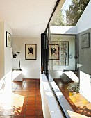 Reflections in glass façade of foyer with terracotta floor in modern bungalow