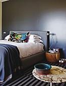 Doppelbett mit buntem Kissen, an schwarz getönter Wand, im Vordergrund Bistrotisch mit Schale