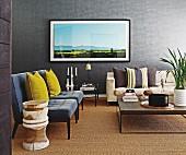 Yellow scatter cushions on grey easy chairs in traditional living room with large artwork on grey wall