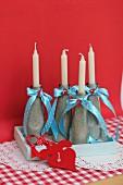Mit Sand gefüllte Flaschen als Kerzenständer verziert mit Schleifenbändern & Dekozahlen