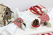 Festive table decoration with nesting box, napkin rings, garland of stars & pine cones