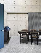 Dining room with concrete walls, dark furniture and blue door