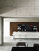 Open-plan kitchen with modern island counter and concrete walls