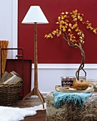 Autumnal home accessories: standard lamp with wooden base, transparent plastic pouffe stuffed with straw and branches decorated with garlands of leaves
