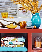 Autumn arrangement of twigs, branches and accessories on orange-painted shelves
