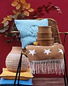 Autumnal home accessories: fifties-style wicker chair, soft cushion, woollen blanket, nest of wooden boxes and terracotta vase
