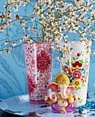 Zwei Porzellanvasen mit dekorativen Blütenmustern davor Ganesha-Figur auf Tablett