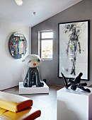 Exhibits and artworks on plinths and framed picture on grey wall