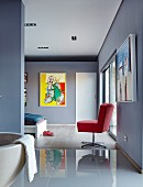 Ensuite bathroom with glossy tiled floor leading into blue-grey bedroom with red swivel chair and modern painting