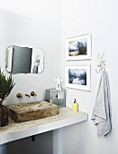 Washstand with concrete sink below vintage mirror and framed photos on walls