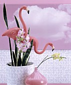 Plastic flamingos in potted house plant, pink vase and pink photo mural of clouds