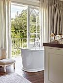 Free-standing vintage-style bathtub next to open balcony door of large, elegant bathroom
