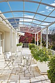 French bistro furniture and planters on sunny terrace below curved metal pergola below blue sky