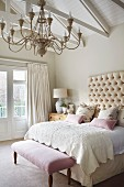 Chandelier above double bed with button-tufted headboard and antique bedroom bench