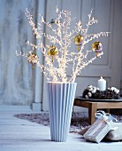 Twigs covered in fairy lights and decorated with baubles in floor vase