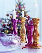 Festive arrangement of deep pink and gold candlesticks made from silvered glass