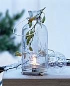 Glass candle lantern decorated with sprig of rose hips