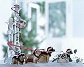 Festive arrangement of dog ornaments wearing Father Christmas hats and colourful ribbons amongst artificial snow