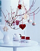Vase of branches decorated with baubles and hand-made red and white felt pendants