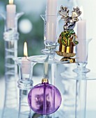 Glass candlesticks festively decorated with glass baubles and moose figurine