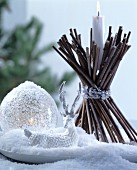 Christmas arrangement of glass bauble, reindeer ornament and candle holder hand-made from bundled twigs
