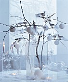 White Christmas: glass vase of branches decorated with baubles, stars and silver birds